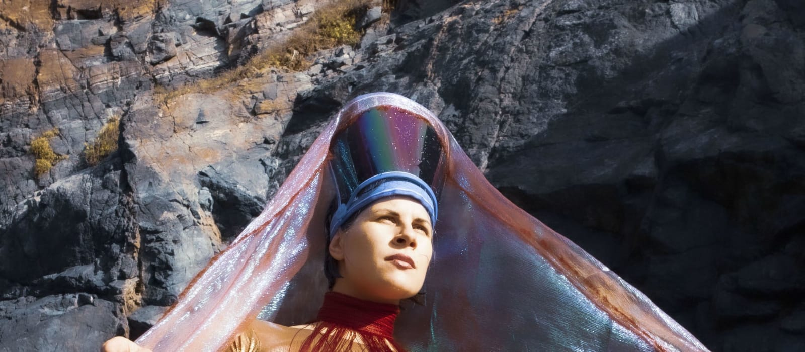 Gery Georgieva is standing in a gold unitard, open armed and looking determined, out into the distance. She is wearing a gold uniard, wrapped in red and yellow tassels and a blue futuristic head piece with a peach coloured iridescent cloak.